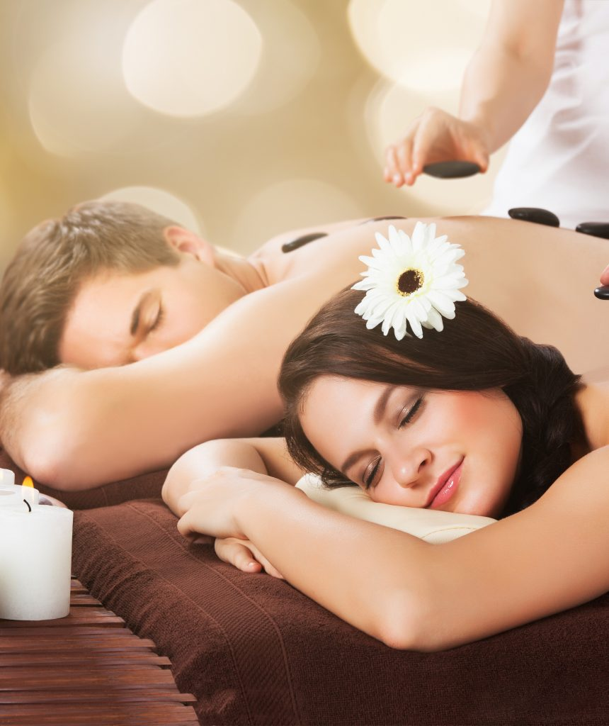 Couple Receiving Hot Stone Therapy At Beauty Spa